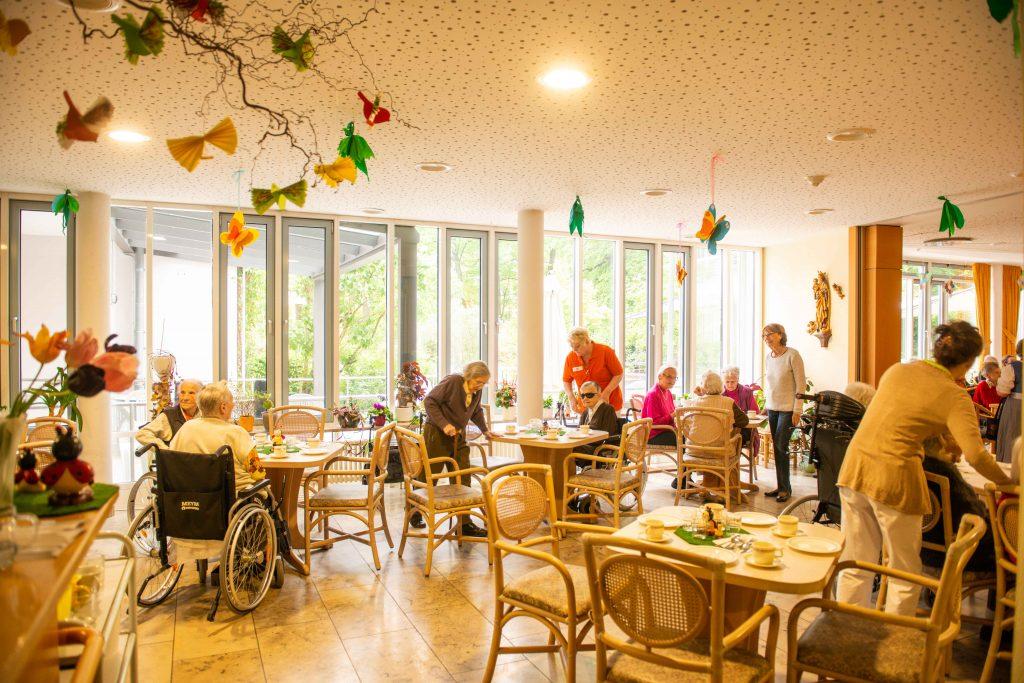 Mehrere Bewohner sitzen zum Kaffeetrinken in der Caféteria